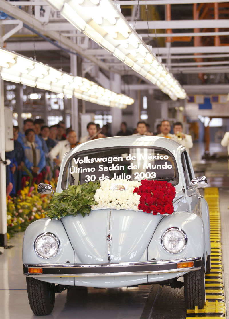 """The very last VW beetle is decorated with a wreath of roses and a message on its windscreen which reads """"Volkswagen of Mexico last Sedan in the World, 30th July 2003"""" in Spanish as it rolls off the production line at VW's Puebla plant July 30, 2003. The final Beetle rolled off the Puebla production line today after 58 years of production, and almost 70 years since its conception. REUTERS/Andrew Winning POOL"""